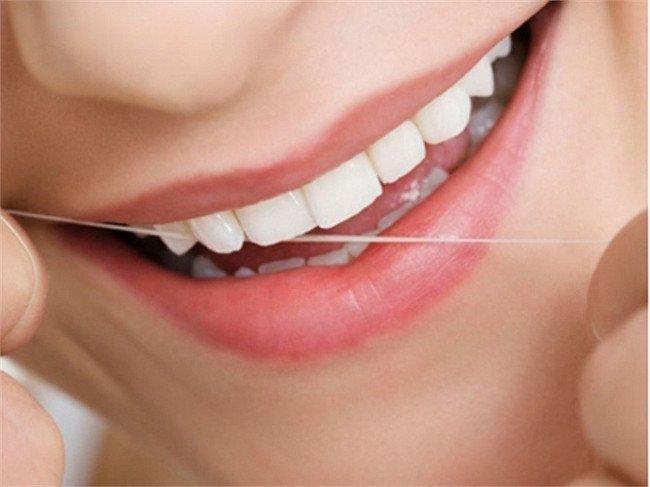 Nên dùng chỉ nha khoa để lấy thức ăn mắc ở răng